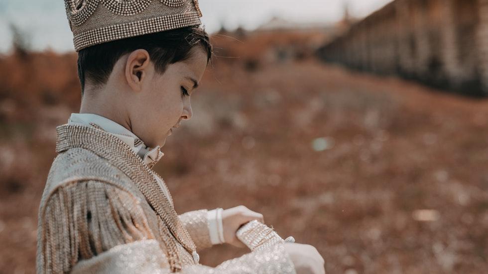 Foto: av R. Fera / Pexels på ett barn som bär en krona