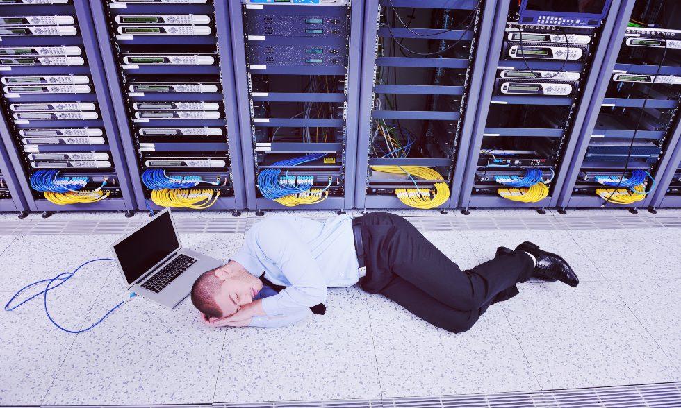 Foto: Envato/Dotshock – en utmattad man sover på golvet vid sin dator i ett serverrum