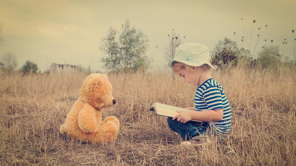 Ett barn berättar  en berättelse för sin nalle.